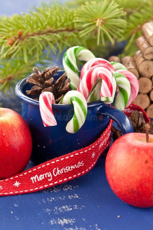 Bastones de caramelo en taza azul imagen de archivo libre de regalías