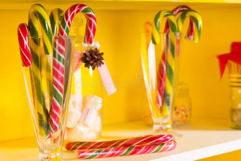 Bastones de caramelo festivos coloridos en los tarros de cristal imágenes de archivo libres de regalías