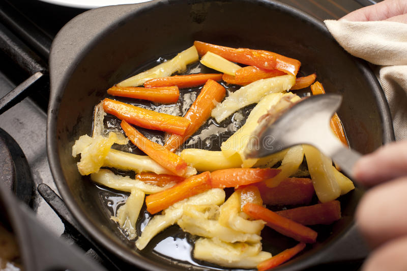Bastones de la zanahoria y de la pastinaca que son salteados imágenes de archivo libres de regalías