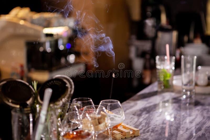 Bastoni aromatici del fumo sul contatore della barra fotografia stock