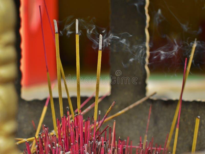 Bastoni brucianti di incenso con tradizione cinese della cultura del fondo del fumo immagini stock