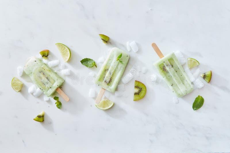 Bastoni del gelato con il kiwi e la calce su un fondo di marmo grigio con i pezzi di foglie di menta e del ghiaccio Copi lo spazi fotografia stock