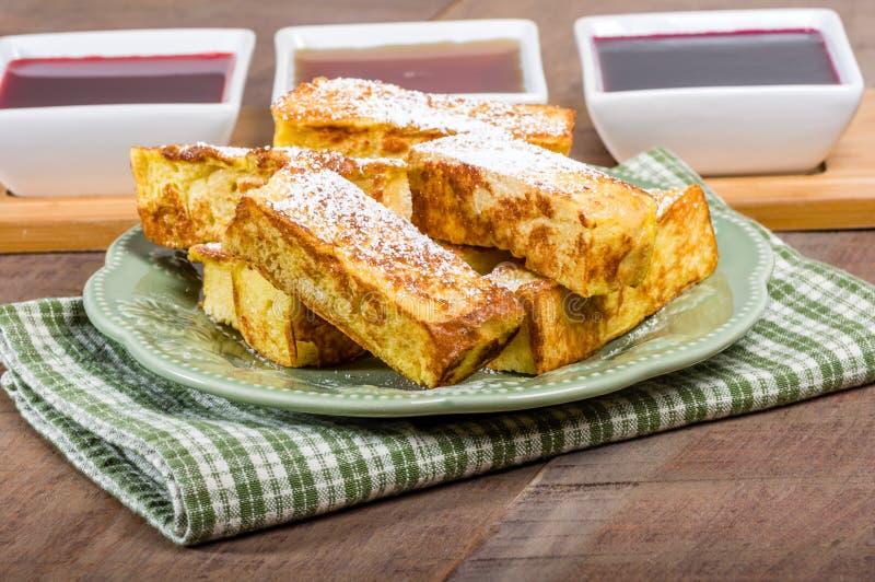 Bastoni del pane inzuppato in latte/uova e zucchero e fritto in padella con gli sciroppi immagini stock libere da diritti