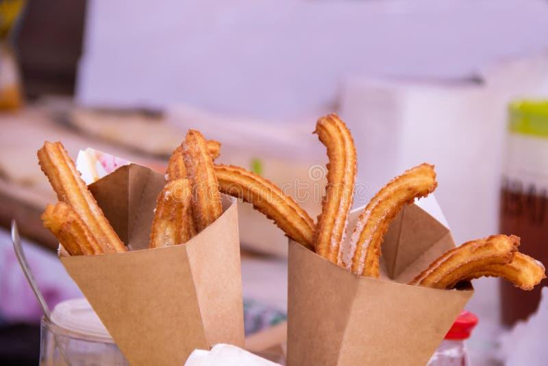Bastoni deliziosi di churros fritti nel grasso bollente in sacco di carta con zucchero in polvere fotografia stock libera da diritti