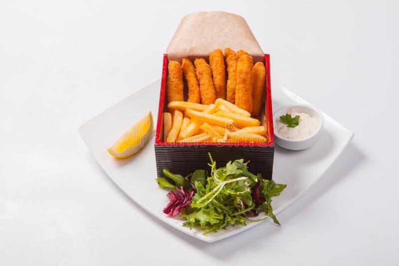 Bastoni di pesce nella scatola di legno con salsa e le patate fritte fotografia stock libera da diritti