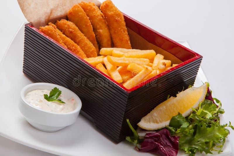 Bastoni di pesce nella scatola di legno con salsa e le patate fritte fotografie stock libere da diritti