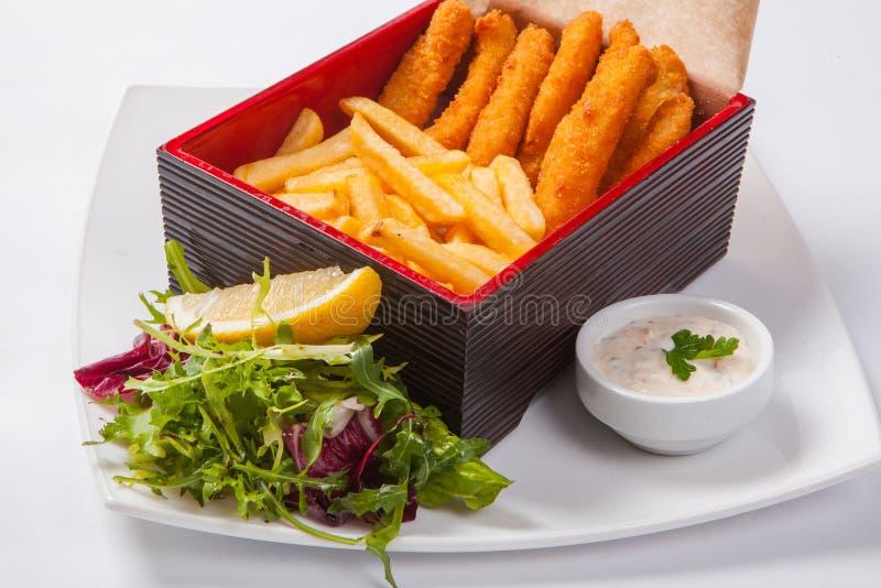 Bastoni di pesce nella scatola di legno con salsa e le patate fritte immagine stock