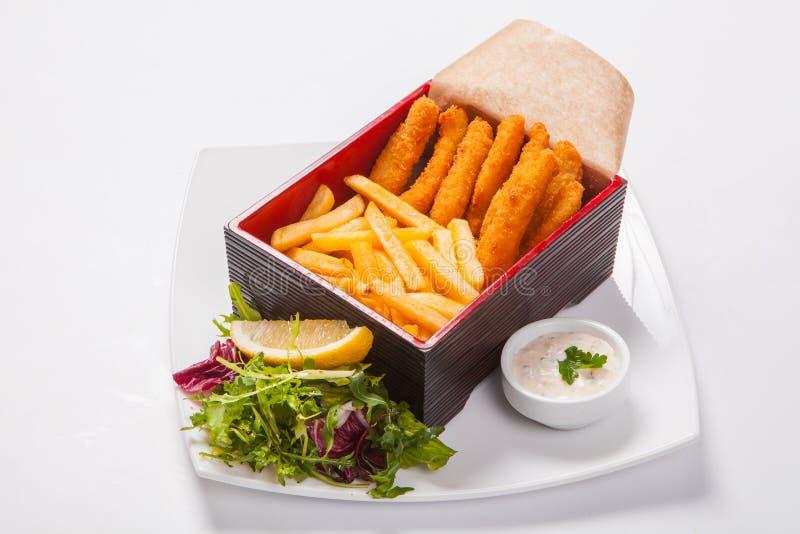 Bastoni di pesce nella scatola di legno con salsa e le patate fritte immagini stock libere da diritti