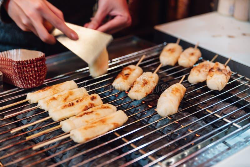 Bastoni grigliati del formaggio sulla stufa della griglia del gas, alimento della via a Ximending in Taiwan, Taipei immagine stock