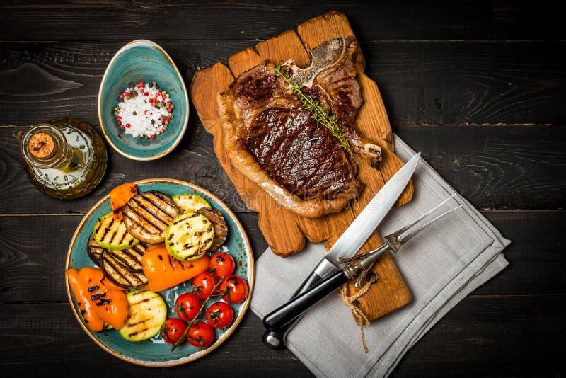Bastoni la bistecca di manzo con i condimenti e le verdure arrostite immagine stock