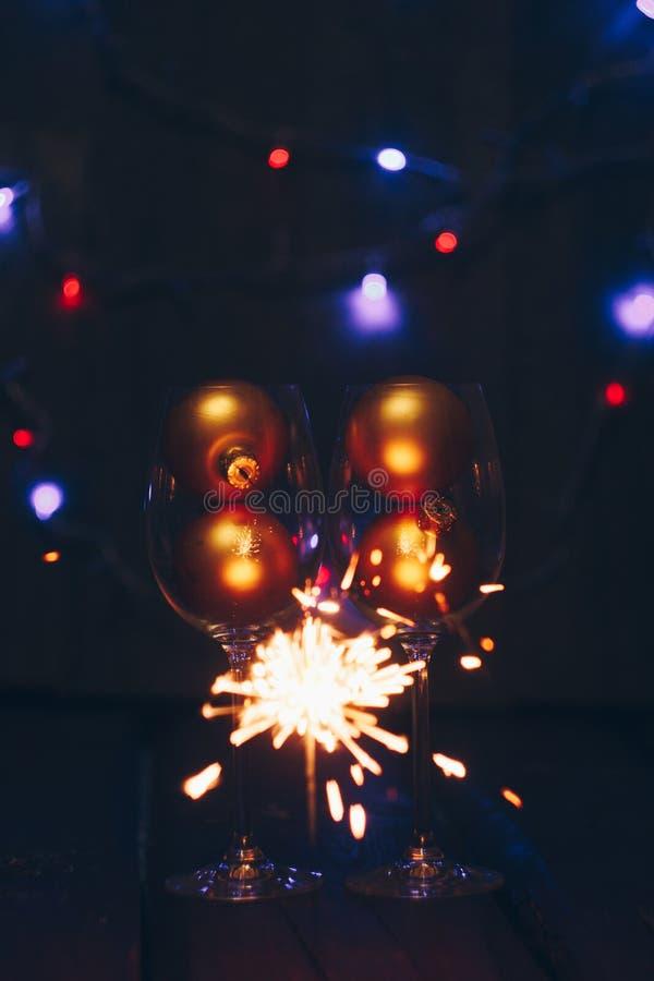 Bastoni scintillanti delle stelle filante del Bengala in fiamme su un fondo nero con i vetri del bokeh e di vino delle luci Nuovo fotografia stock