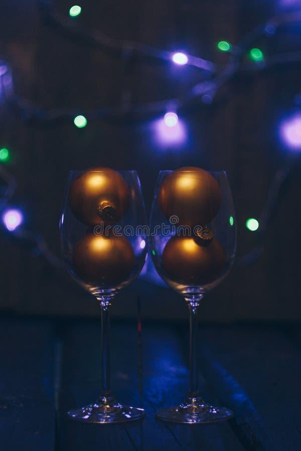 Bastoni scintillanti delle stelle filante del Bengala in fiamme su un fondo nero con i vetri del bokeh e di vino delle luci Nuovo immagine stock