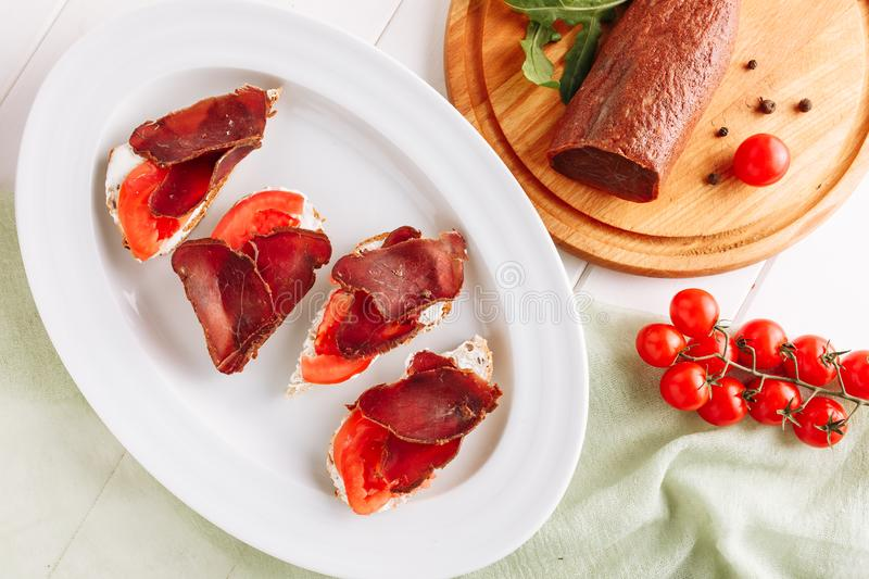 Basturma Dried Beef on Bread Canape Snack Flat Lay. Pork Jerky Sliced Meat on Italian Sandwich Appetizer. Small Toast Meal on White Plate with Red Tomato royalty free stock image