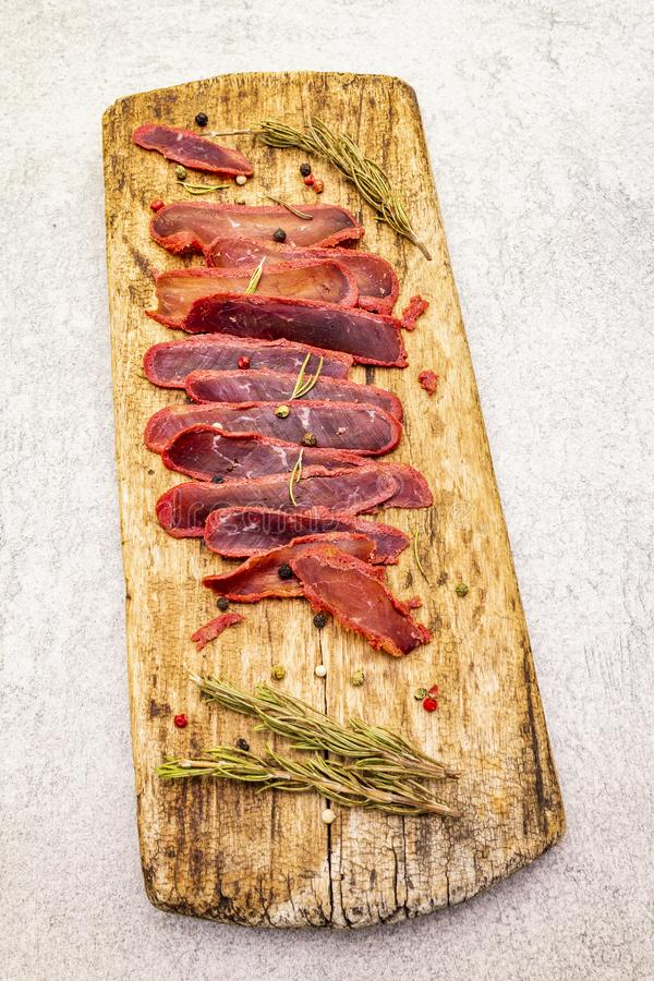 Basturma, dried tenderloin of beef meat, jerky, thinly sliced. Dry rosemary, pepper mix on vintage wooden board. Delicious food on. A stone background stock images