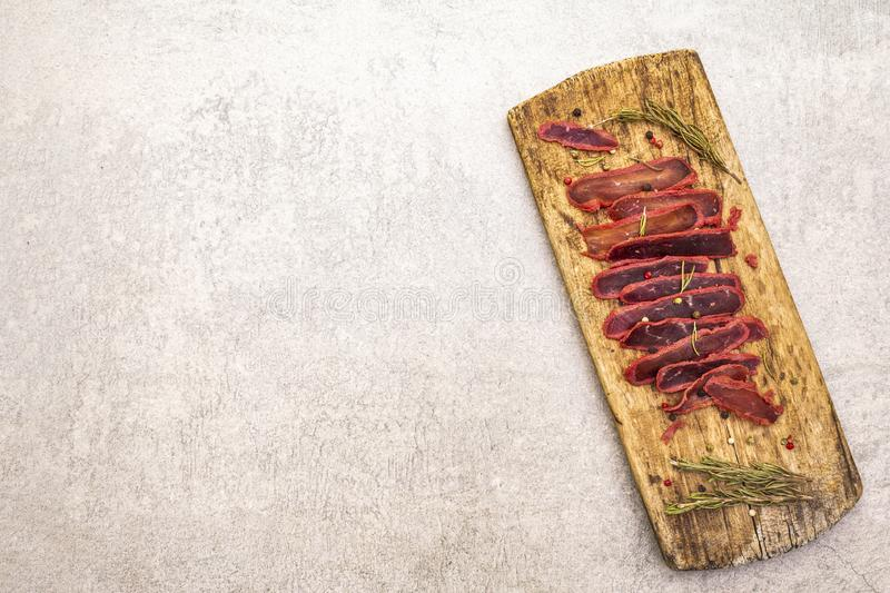 Basturma, dried tenderloin of beef meat, jerky, thinly sliced. Dry rosemary, pepper mix on vintage wooden board. Delicious food on. A stone background, top view royalty free stock photo