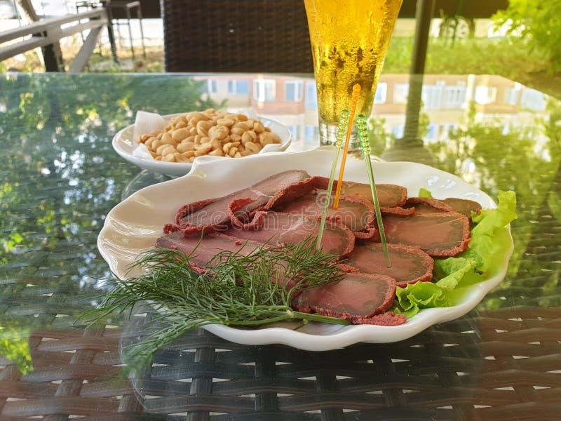 Basturma fresco delicioso en una placa con lechuga, cacahuetes en un platillo blanco y un vidrio de cerveza fría Tabla en fotografía de archivo libre de regalías