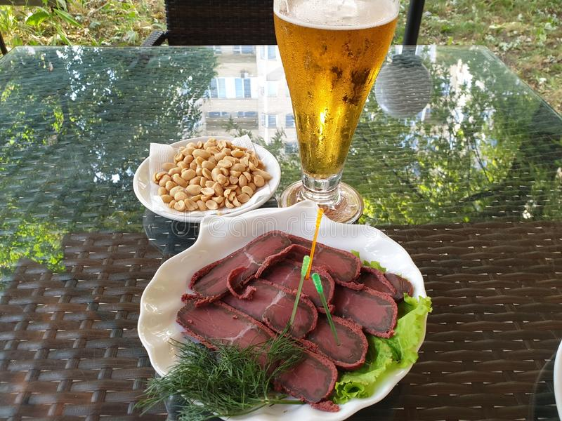 Basturma fresco delicioso en una placa con lechuga, cacahuetes en un platillo blanco y un vidrio de cerveza fría Tabla en fotos de archivo libres de regalías