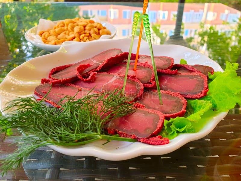 Basturma fresco delicioso en una placa con lechuga Tabla en la barra del verano imagen de archivo libre de regalías