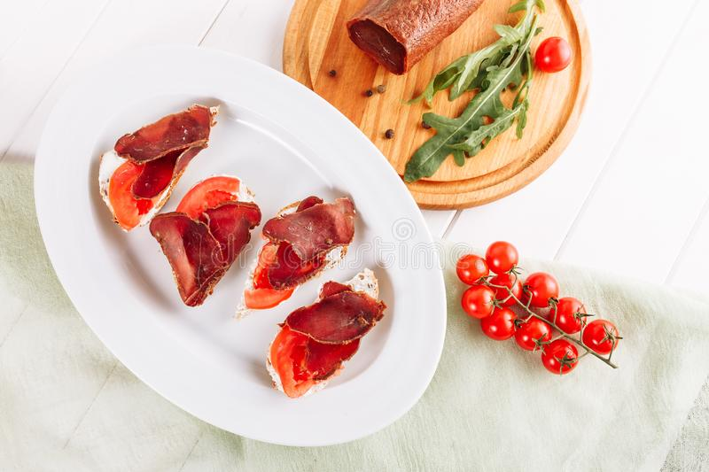 Basturma Ham Bread Sandwich Snack Top Flat Lay. Pork Dried Sliced Meat on Italian Canape Appetizer. Tasty Jerky Meal on White Plate with Red Tomato royalty free stock images