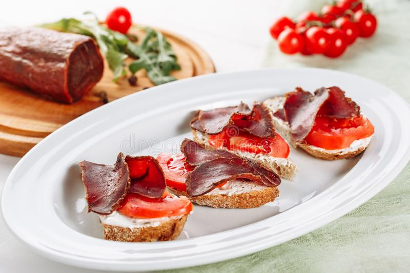 Basturma Ham Sandwich Snack Closeup Side View. Pork Dried Sliced Meat on Italian Bread Canape Small Appetizer. Tasty Jerky Meal Sliced Tomato on White Plate stock image