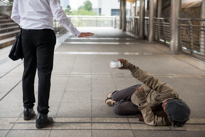 Basura del hombre de negocios que da el dinero al hombre sin hogar fotografía de archivo libre de regalías