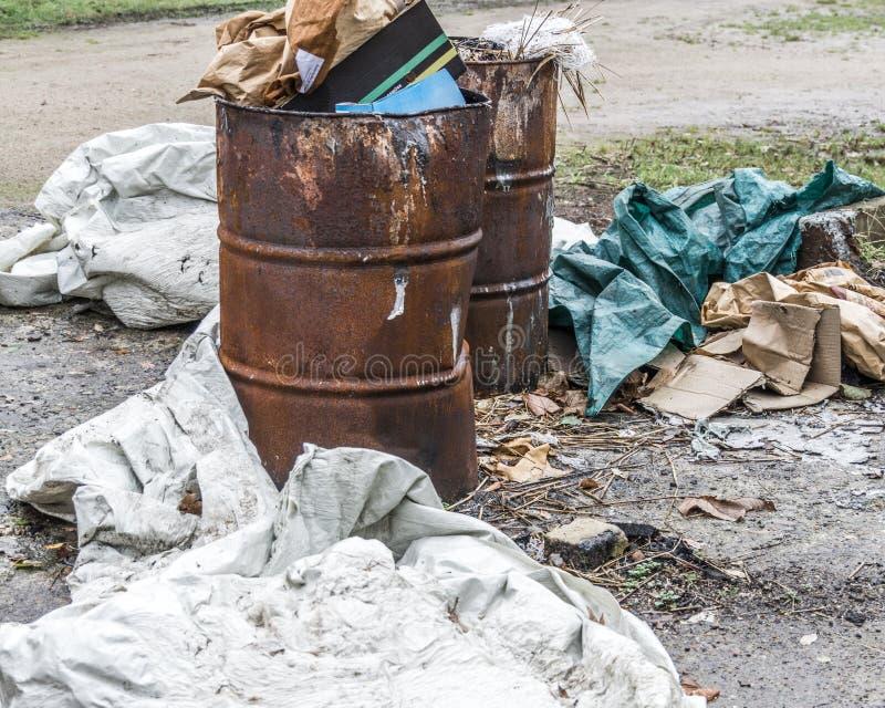 Basura en barriles de aceite viejos oxidados y no regulado distribuido en el th imagen de archivo libre de regalías