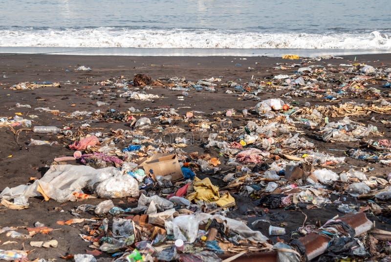 Basura en una playa contaminada arenosa imagen de archivo