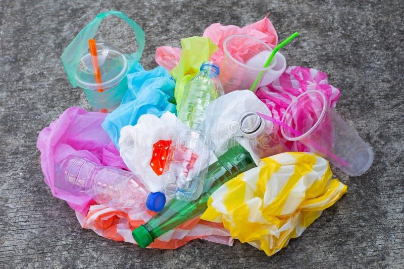 Basura plástica colorida, bolsos, tazas, botellas, paja en piso del cemento imágenes de archivo libres de regalías