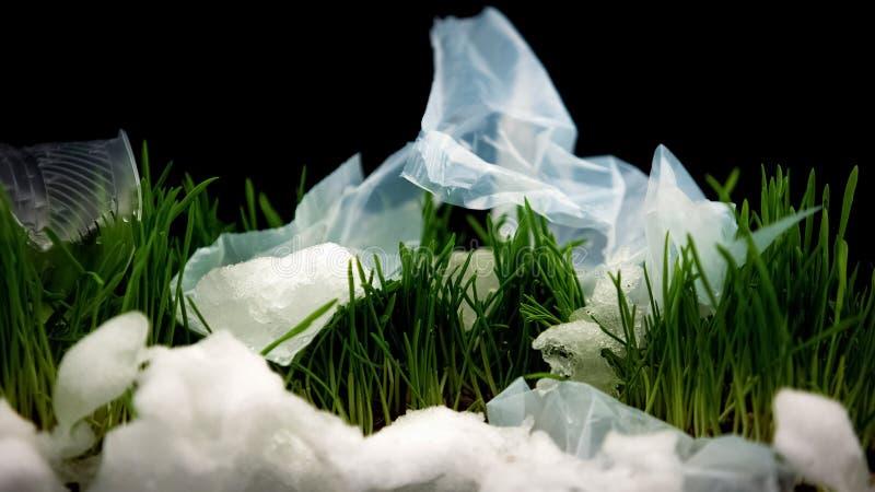 Basura plástica que miente en hierba entre la nieve, catástrofe de la ecología, reciclando problema imagenes de archivo