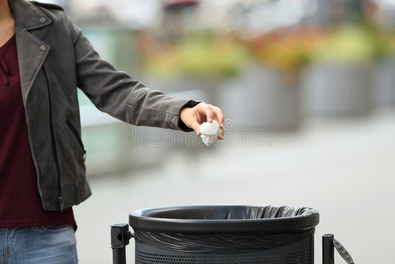Basura que lanza de la mano de la señora a un cubo de la basura foto de archivo