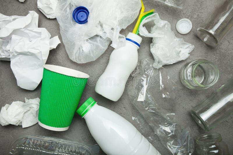 Basura reciclable del fondo que consiste en el vidrio, el plástico, y el documento sobre el hormigón gris fotografía de archivo libre de regalías