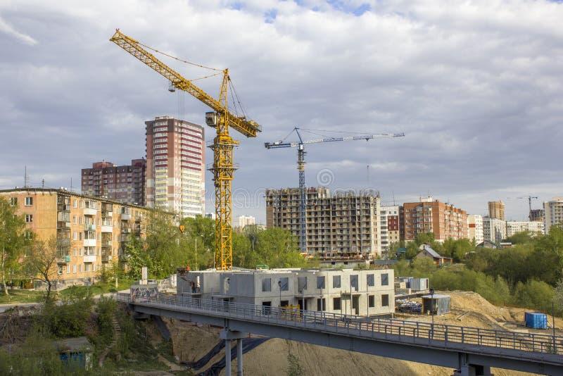 Basztowi żurawie blisko mieścą w budowie blisko mostu przeciw tłu skończeni nowożytni kondygnacja budynki pod a zdjęcia stock