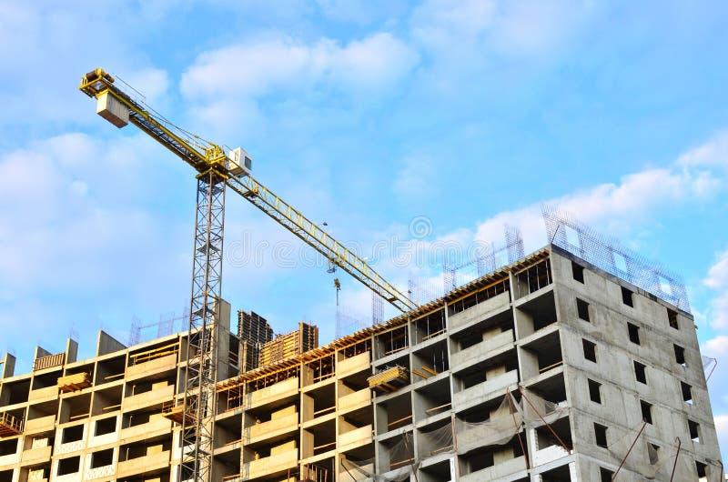 Basztowi żurawie i nowi mieszkaniowi wieżowowie przy ogromną budową na tła niebieskiego nieba tle zdjęcie stock
