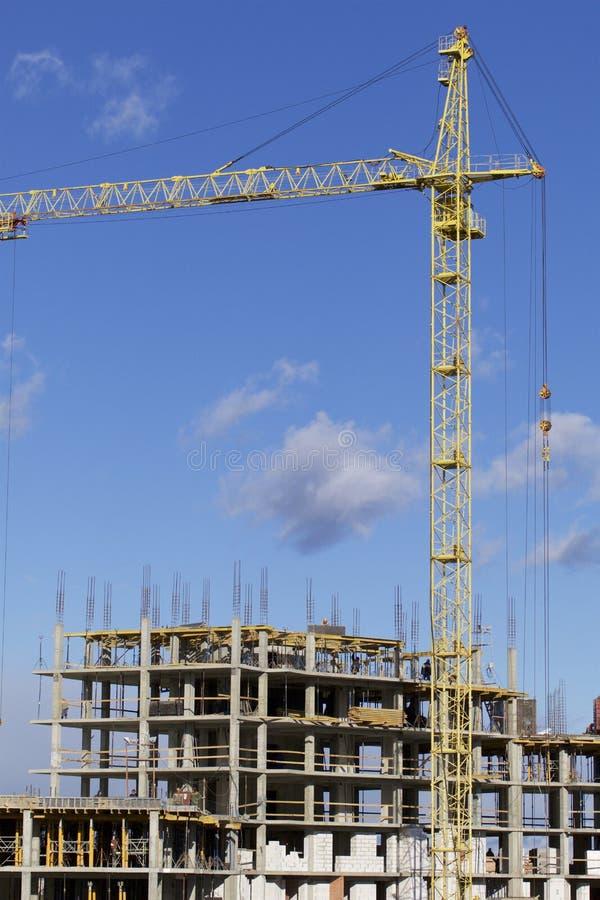 Basztowi żurawie na budowie budynek z ramą zbrojony beton Nasłoneczniony przeciw niebieskiemu niebu zdjęcia stock