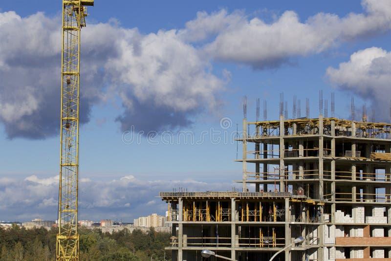 Basztowi żurawie na budowie budynek z ramą zbrojony beton Nasłoneczniony przeciw niebieskiemu niebu obrazy stock