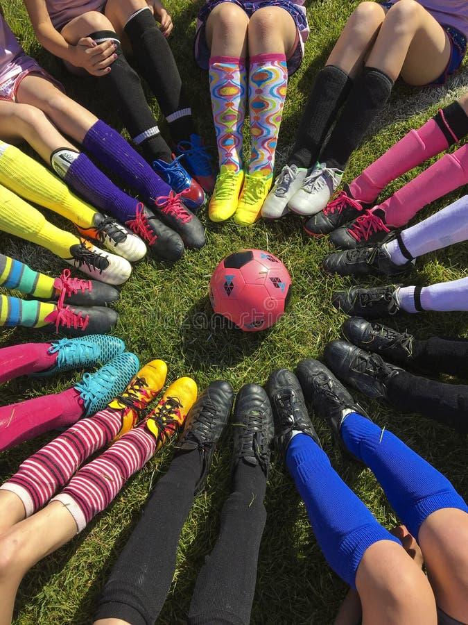 Bata a equipe de futebol que senta-se em torno de uma bola de futebol fotos de stock royalty free