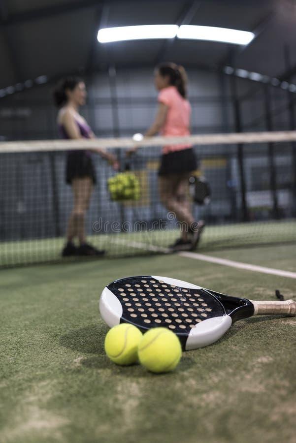 Bata los objetos del tenis en el césped listo para el torneo y las mujeres adentro imagen de archivo