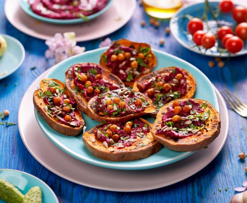 Bataattoost met bietenhummus, geroosterde kekers, verse peterselie, nigellazaden en zonnebloemzaden op een plaat op blauw Ta stock foto