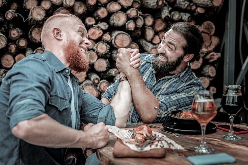 Bataille globale de bras de fer entre deux amis masculins photographie stock libre de droits