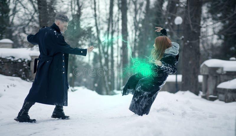 Batalha de mágicos escuros e claros com a ajuda das varinhas mágicas e do feixe verde imagem de stock