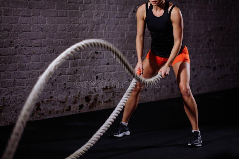 A batalha ropes a sessão Os jovens atrativos couberam e tonificaram o treinamento do desportista no gym fotos de stock royalty free