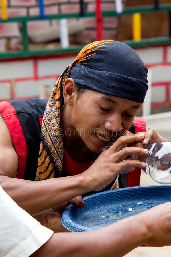 BATAM, INDONESIA - DECEMBER 7, 2012: Local citizen performing act eating glass in traditional attire. During the day stock images
