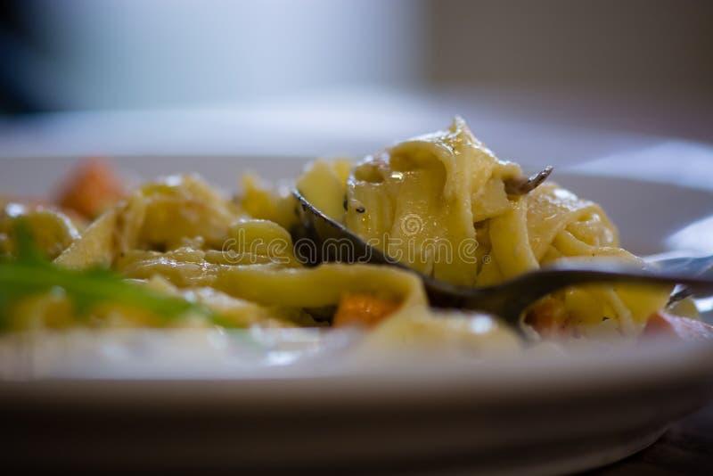 Batat, kózka ser i czerwonej cebuli tagliatelle na łyżce od strony, zdjęcie stock