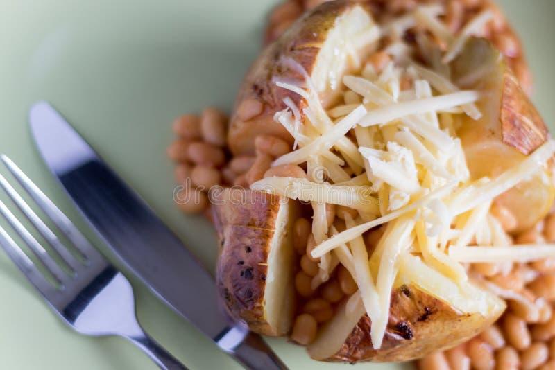 Batata com manteiga com feijões cozidos e queijo raspado fotos de stock royalty free
