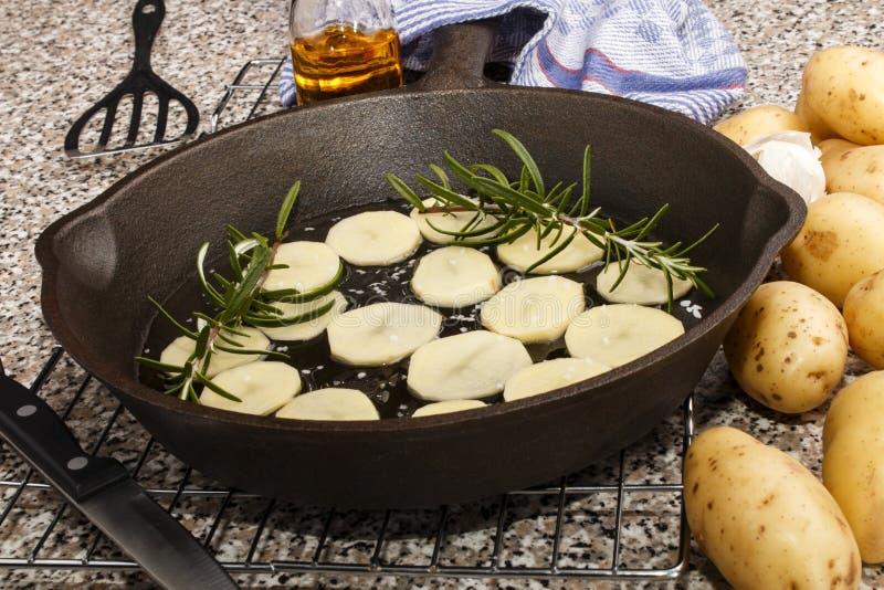 Batata cortada com alecrins em uma bandeja do ferro fundido imagem de stock
