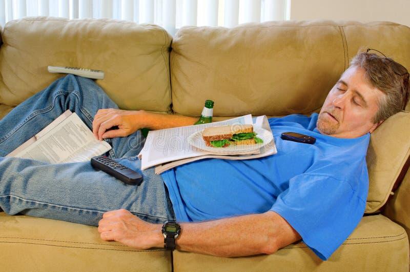 Batata de sofá ocupada do homem do sono fotos de stock