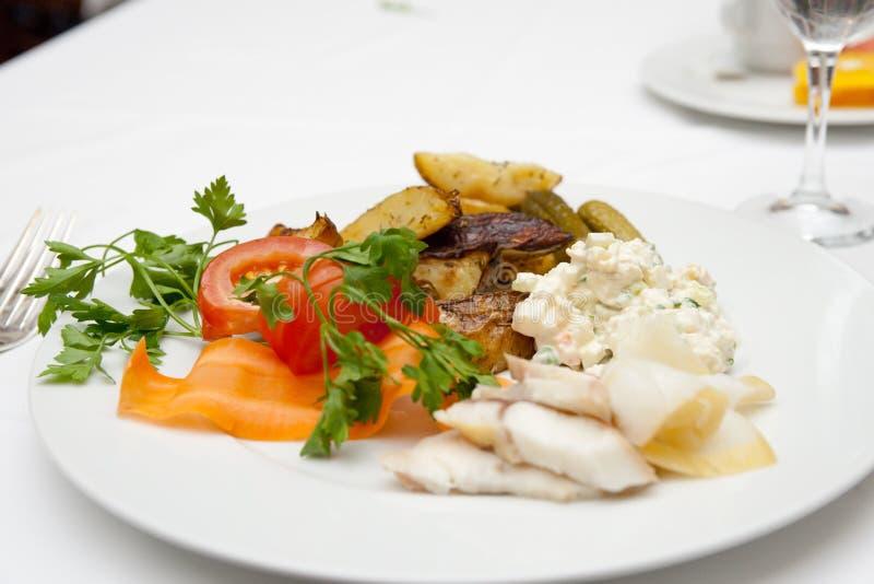 Batata, peixe, salada na placa da porcelana fotografia de stock royalty free