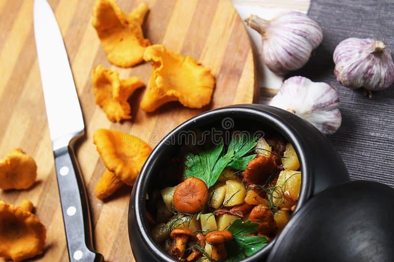Batatas com cogumelos em um potenciômetro de argila Cogumelos da floresta fotografia de stock royalty free