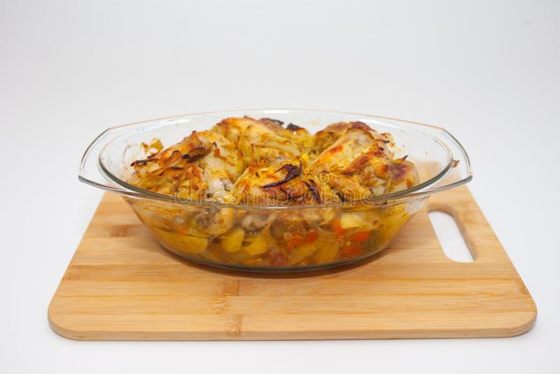Batatas com os vegetais cozidos no forno em um recipiente de vidro com uma tampa placa de corte e fundo branco imagens de stock royalty free