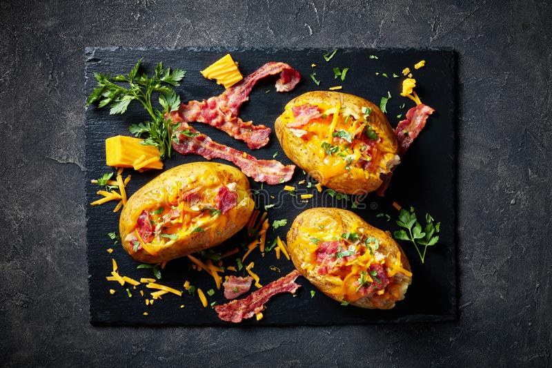 Batatas cozidas carregadas com bacon, queijo, carne imagens de stock